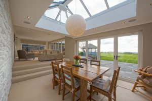 Farmhouse with sun room extension, dining area.