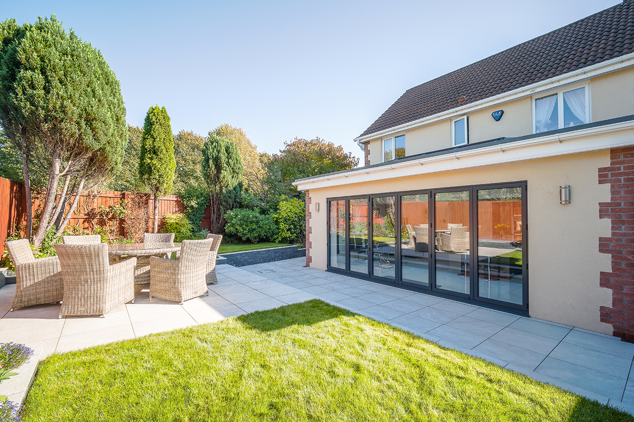 house with patio furniture and bi-folding doors