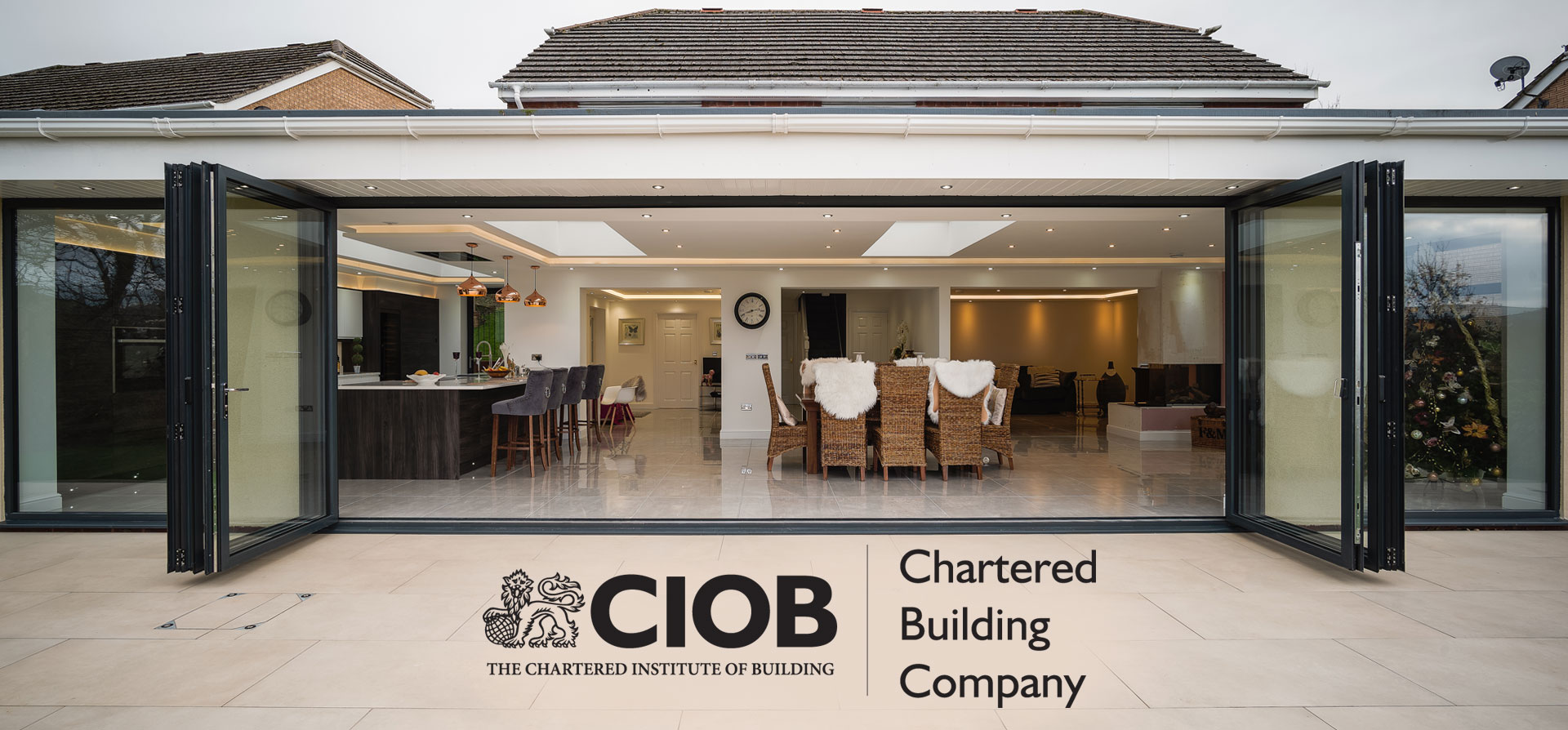 Kitchen sunroom with doors open. CIOB logo.